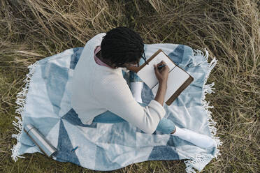 Young man writing on diary while sitting at blanket amidst dried plant - BOYF01848