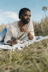 African man with diary lying on blanket amidst dried plants looking away - BOYF01851