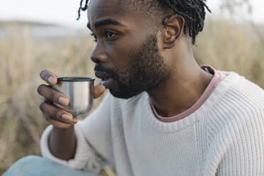 man on the beach having a tea from a thermos flask. Dublin Ireland - BOYF01854
