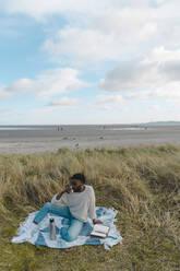 man on the beach having a tea from a thermos flask. Dublin Ireland - BOYF01857