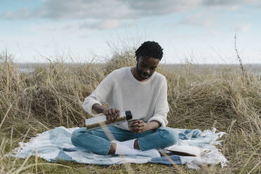Young man pouring tea from insulated drink container while sitting on blanket amidst dried plant against cloudy sky - BOYF01860