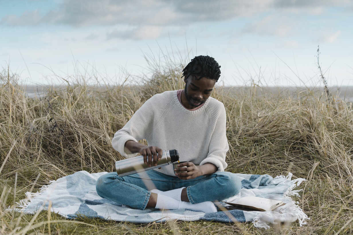 Young man pouring tea from insulated drink container while sitting on blanket amidst dried plant against cloudy sky - BOYF01860 - Boy/Westend61