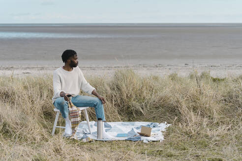 Young man drinking tea while sitting on stool amidst dried plants at beach - BOYF01863