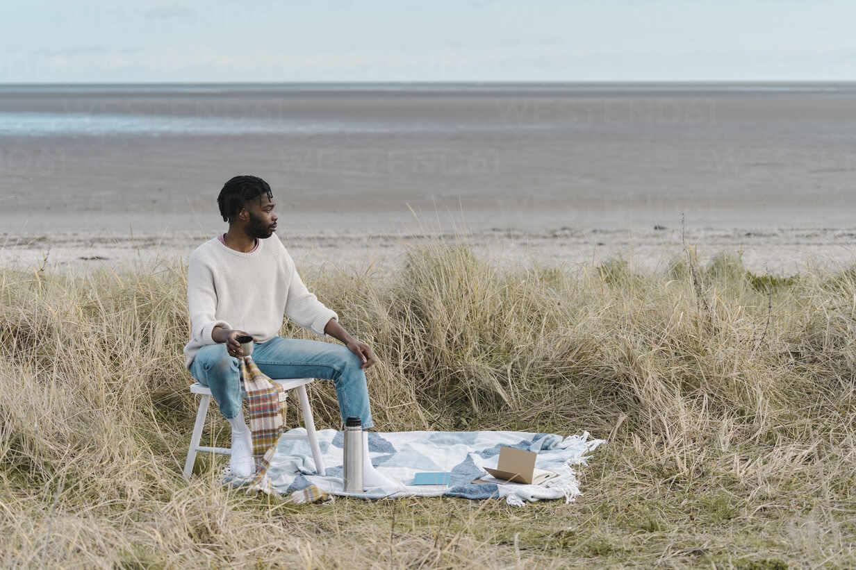 Junger Mann trinkt Tee und sitzt auf einem Hocker inmitten von getrockneten Pflanzen am Strand - BOYF01863 - Boy/Westend61