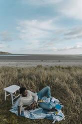 Man on the beach using a mobile phone. Dublin Ireland - BOYF01869