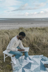 Young man reading book while sitting on stool at beach - BOYF01875