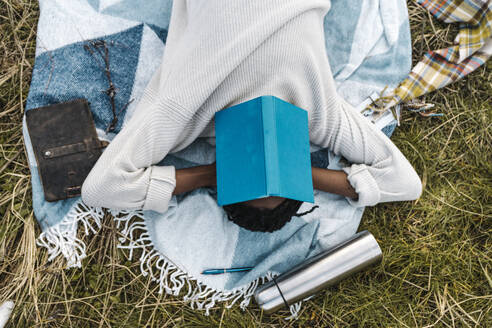 Young man covering his face with book while napping on blanket - BOYF01887