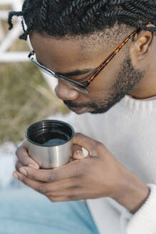 Young man drinking hot tea from cup - BOYF01890
