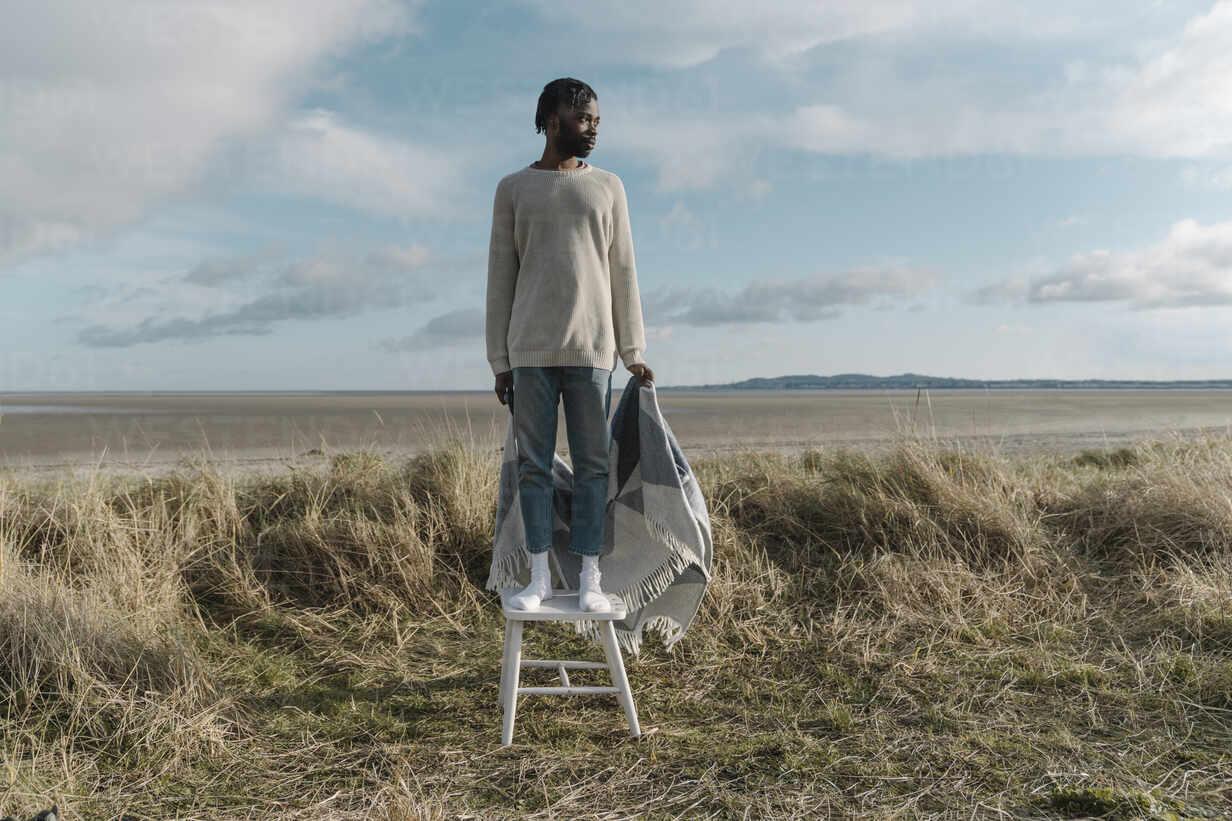 Afrikanischer junger Mann mit Decke auf einem Hocker stehend, während er gegen den bewölkten Himmel wegschaut - BOYF01896 - Boy/Westend61