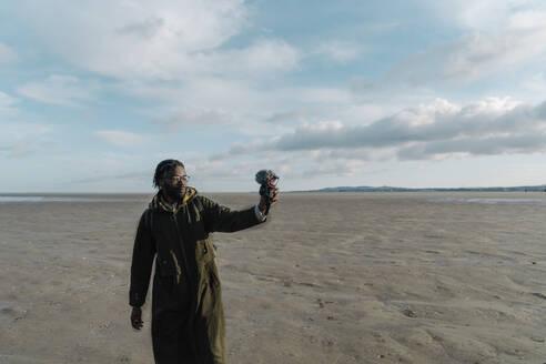 Male travel influencer vlogging at beach against sky - BOYF01899