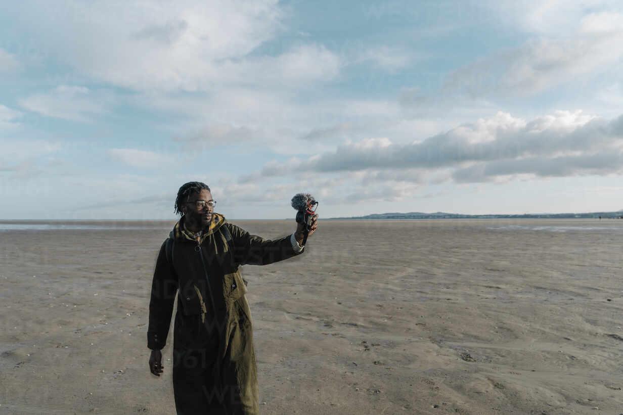 Männliche Reise-Influencer Vlogging am Strand gegen den Himmel - BOYF01899 - Boy/Westend61