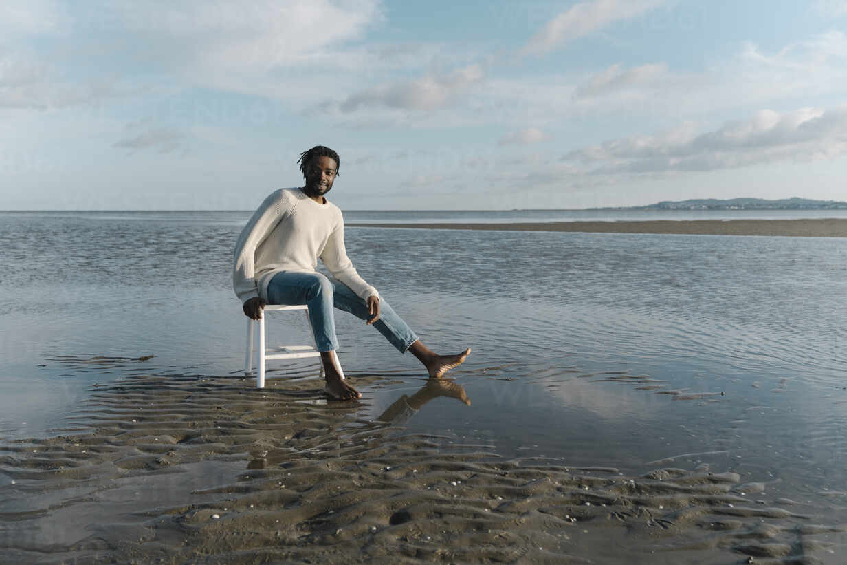 Man with a white stool and relaxing watching the sunset. Mindful and men's mental health concept. Dublin Ireland - BOYF01911 - Boy/Westend61