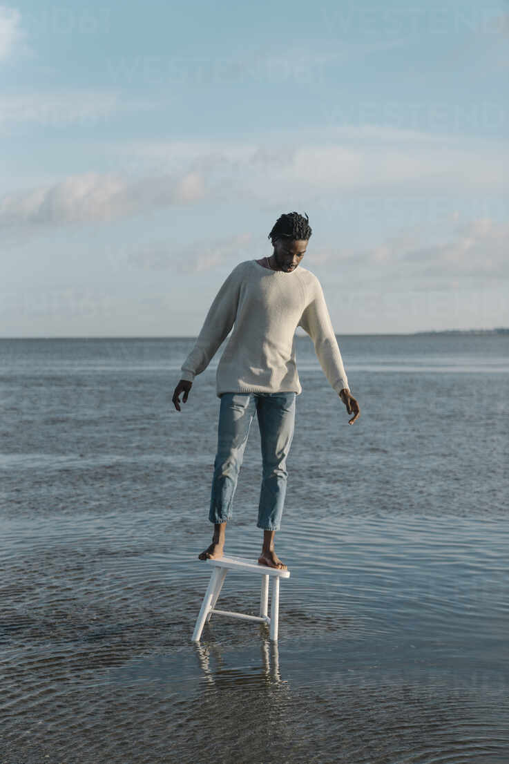Young man standing on white stool while balancing at beach against cloudy sky - BOYF01917 - Boy/Westend61