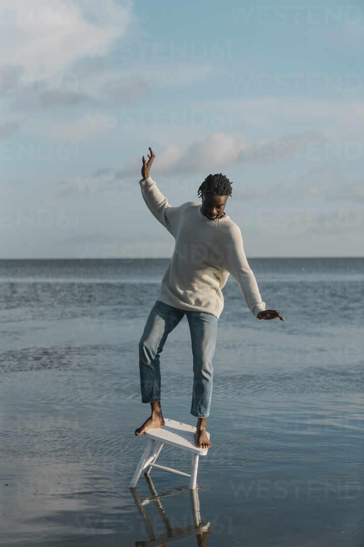 Afrikanischer Mann balanciert auf weißem Hocker am Strand gegen bewölkten Himmel - BOYF01920 - Boy/Westend61