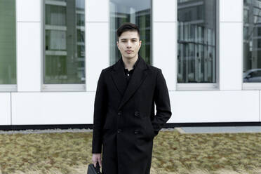 Young business professional with hand in pocket standing against office building - FLLF00586