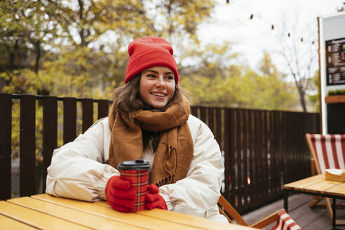 Young woman wearing warm clothing having coffee while sitting at sidewalk cafe - OYF00314