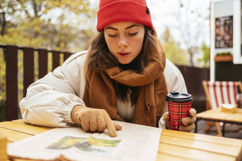 Woman with coffee cup reading newspaper while sitting at sidewalk cafe - OYF00317