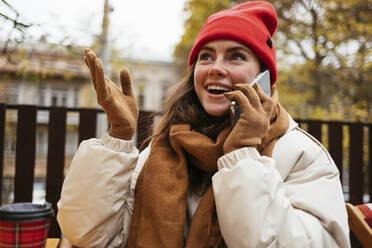 Smiling woman wearing knit hat gesturing while sitting at sidewalk cafe - OYF00323