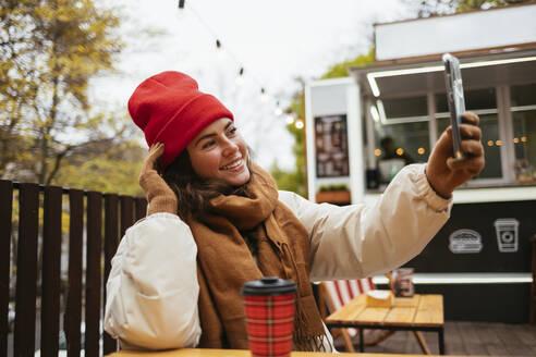 Woman wearing warm clothing taking selfie through mobile phone while sitting at sidewalk cafe - OYF00326