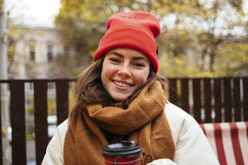 Young woman wearing knit hat and scarf smiling while sitting at sidewalk cafe - OYF00329