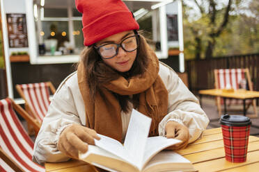 Young woman reading book while sitting at sidewalk cafe - OYF00332