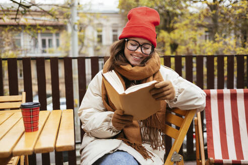 Young smiling woman reading book while sitting on chair at sidewalk cafe - OYF00335