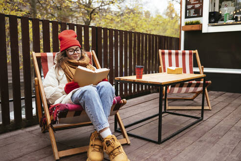 Young woman wearing warm clothing reading book while sitting on chair at sidewalk cafe - OYF00341