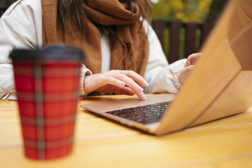 Woman wearing scarf working on laptop while sitting at sidewalk cafe - OYF00350