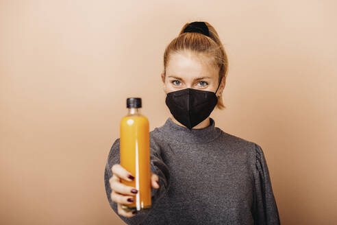Mid adult woman wearing face mask holding smoothie while standing against beige background - DAWF01759
