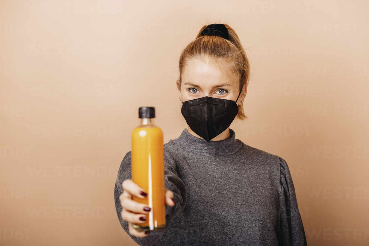 Mid adult woman wearing face mask holding smoothie while standing against beige background - DAWF01759 - Daniel Waschnig Photography/Westend61