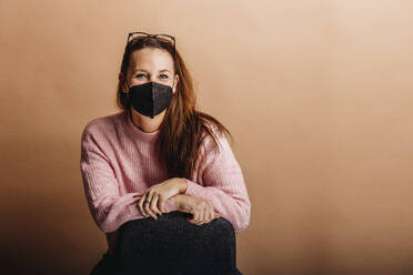 Young woman wearing protective face mask staring while standing against beige background - DAWF01762