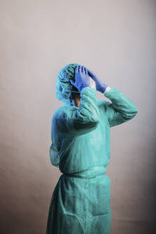 Male doctor wearing protective suit standing with head in hands against gray background - DAWF01768
