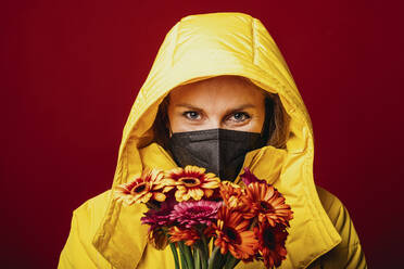 Mid adult woman wearing hood clothing and protective face mask staring while standing with bunch of flowers against red background - DAWF01771