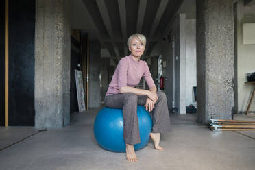 Blond woman sitting on fitness ball in loft apartment - MOEF03572