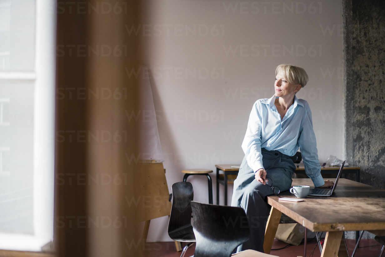 Lächelnde Geschäftsfrau mit Laptop auf dem Schreibtisch sitzend, während sie im Büro zu Hause wegschaut - MOEF03581 - Robijn Page/Westend61
