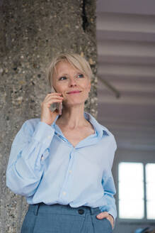 Smiling businesswoman talking on mobile phone while standing against Architectural Column - MOEF03587