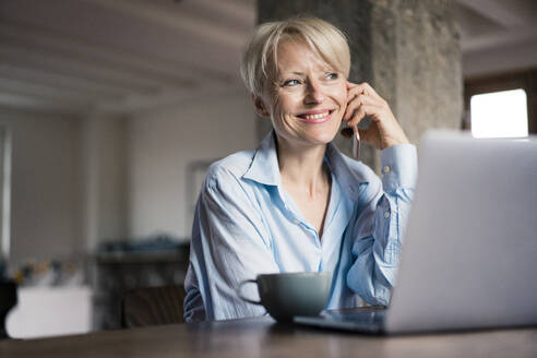 Smiling businesswoman with laptop and coffee cup looking away while talking on mobile phone at desk in home office - MOEF03593