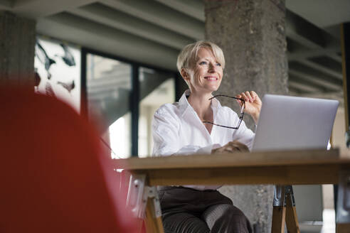Smiling businesswoman with laptop holding eyeglasses while sitting at desk in home office - MOEF03596