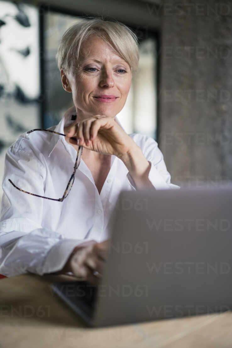 Lächelnde weibliche Unternehmerin, die eine Brille hält, während sie im Büro zu Hause am Laptop arbeitet - MOEF03599 - Robijn Page/Westend61