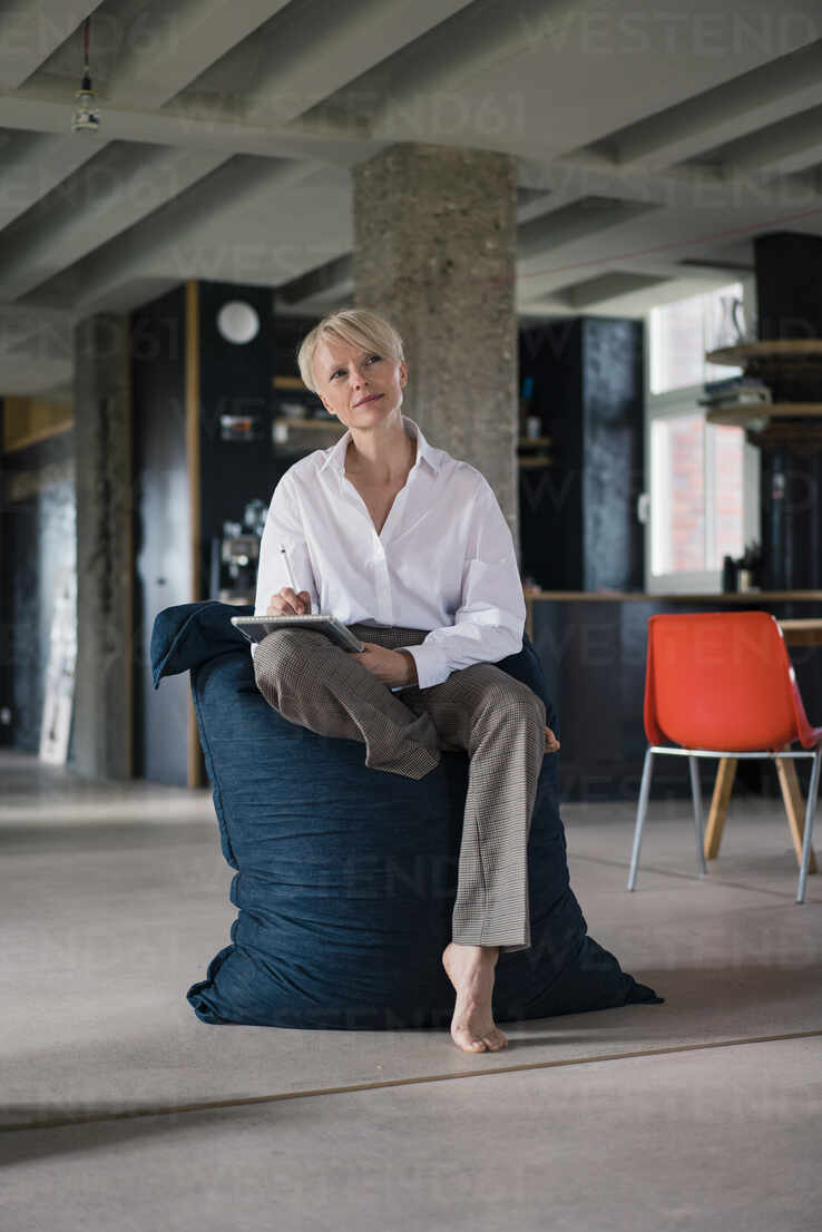 Nachdenkliche Geschäftsfrau, die ein digitales Tablet benutzt, während sie zu Hause sitzt - MOEF03605 - Robijn Page/Westend61