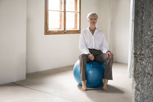 Woman meditating sitting on fitness ball at home - MOEF03611