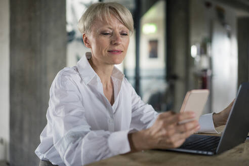 Blond businesswoman with laptop using mobile phone while sitting at desk in home office - MOEF03614