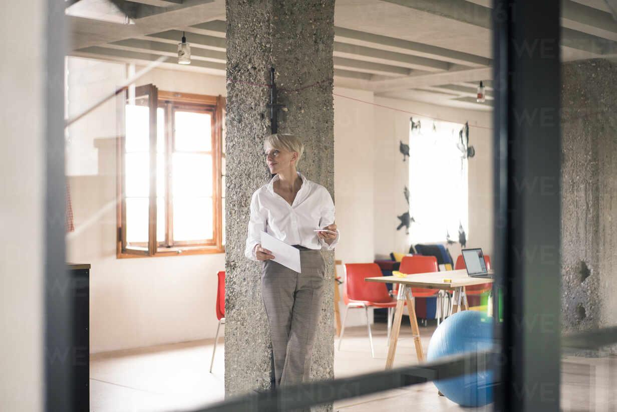Geschäftsfrau durch Glaswand gesehen, während sie ein Dokument gegen eine Säule im Heimbüro hält - MOEF03620 - Robijn Page/Westend61