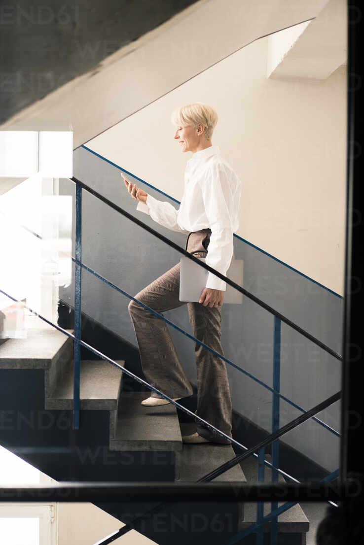Weiblicher Unternehmer mit Smartphone beim Gehen auf der Treppe in Loft-Wohnung - MOEF03623 - Robijn Page/Westend61