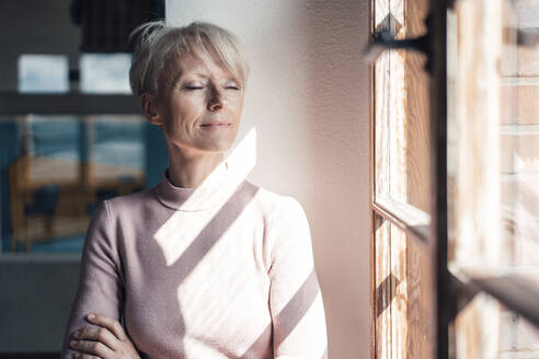 Blond businesswoman with arms crossed leaning on wall by window in home office - MOEF03626