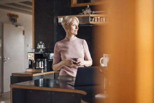 Smiling businesswoman looking away while holding coffee cup in kitchen at home office - MOEF03632