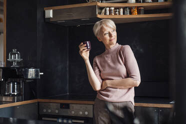 Smiling businesswoman looking away while holding coffee cup in kitchen at home - MOEF03635