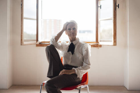 Serious businesswoman with hand in hair sitting on chair against window in home office - MOEF03641