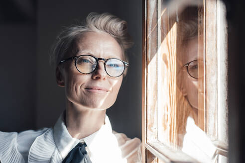 Smiling mature businesswoman looking away while leaning at window in home office - MOEF03650