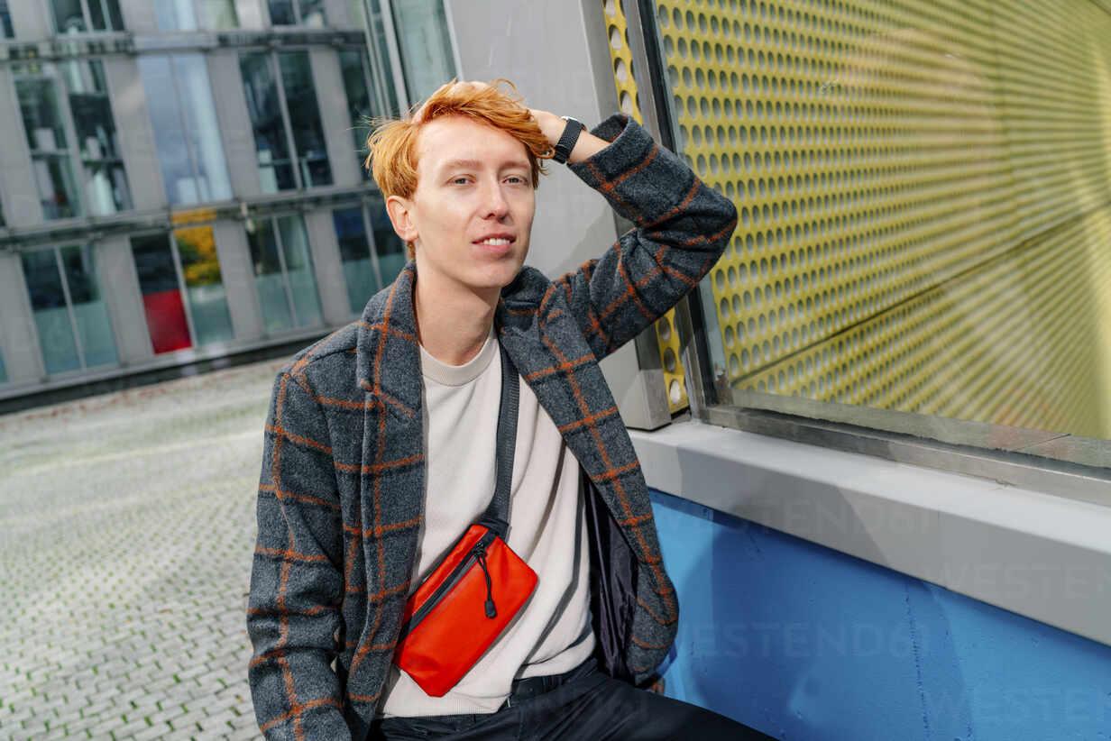 Redhead man with hand in hair on footpath against building - OGF00893 - Oxana Guryanova/Westend61